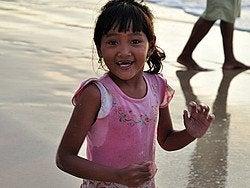 Niña en la playa de Jimbaran al atardecer