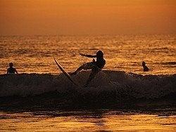 Surfistas en la playa de Kuta al atardecer