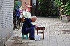 Leyendo el periódico en una sillita